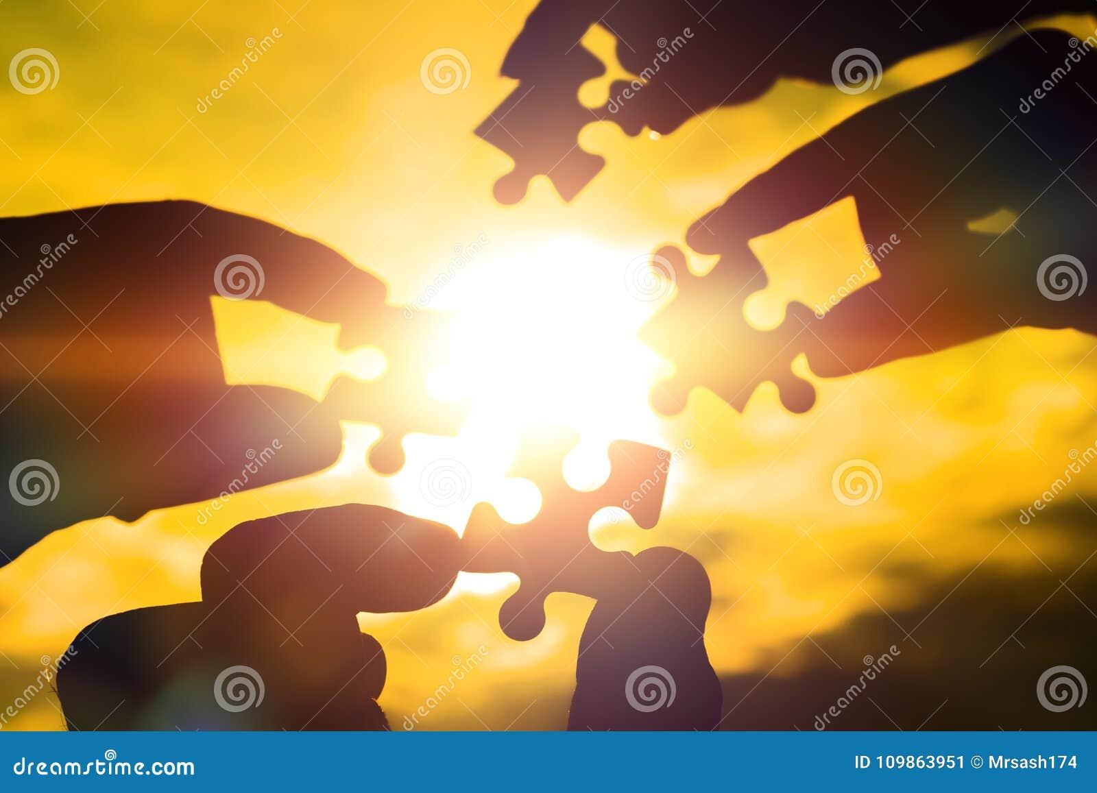 Colaboran cuatro manos que intentan conectar un pedazo del rompecabezas con un fondo de la puesta del sol Un rompecabezas a dispo