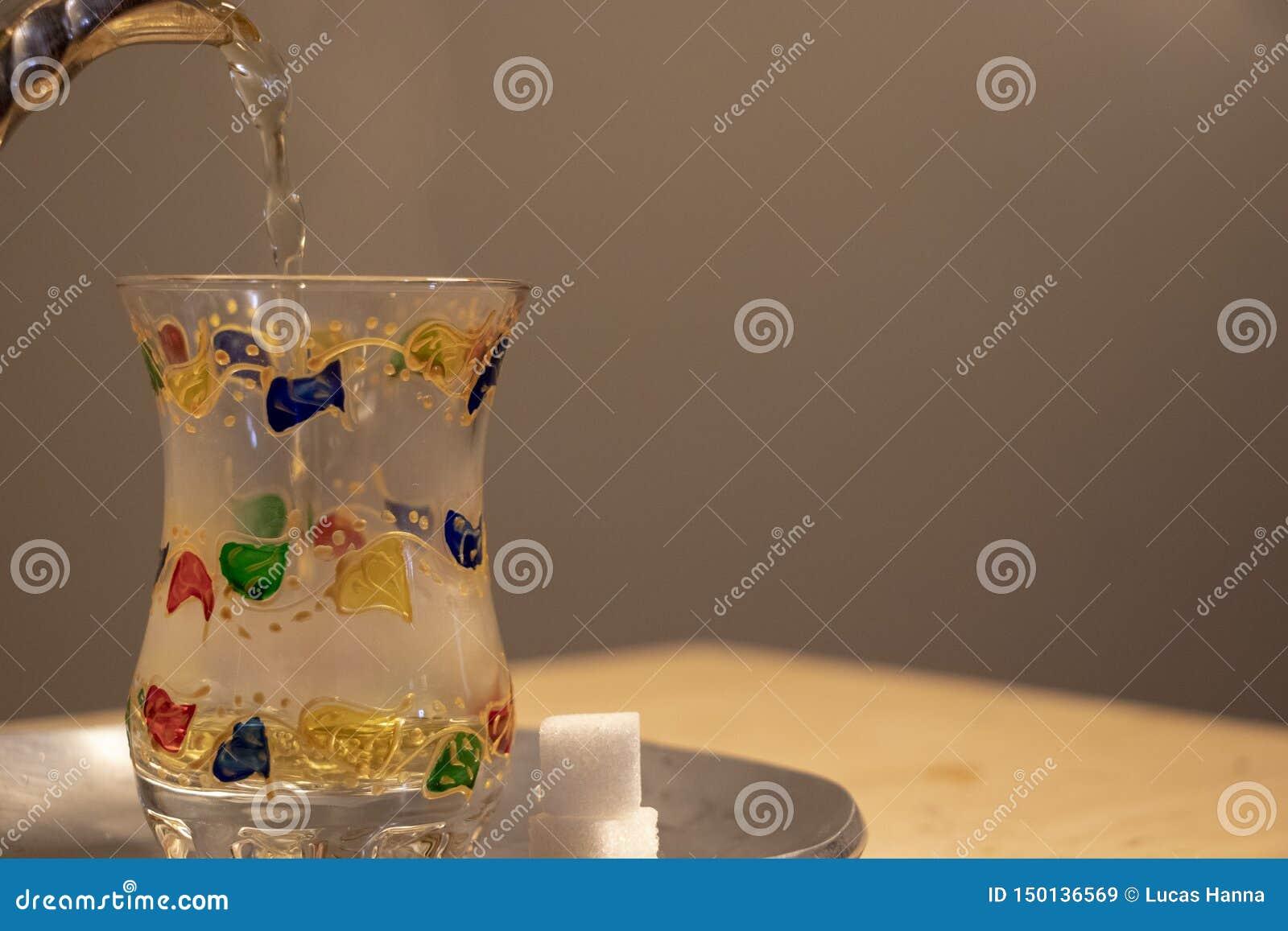 Colada de un vidrio caliente de té de la menta