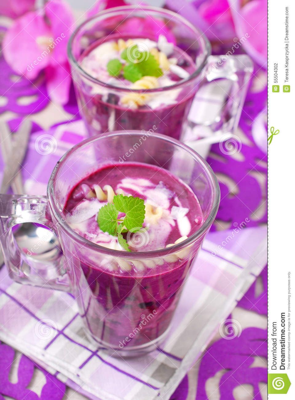 Cold blueberry soup with pasta,cream and coconut flakes in glass.