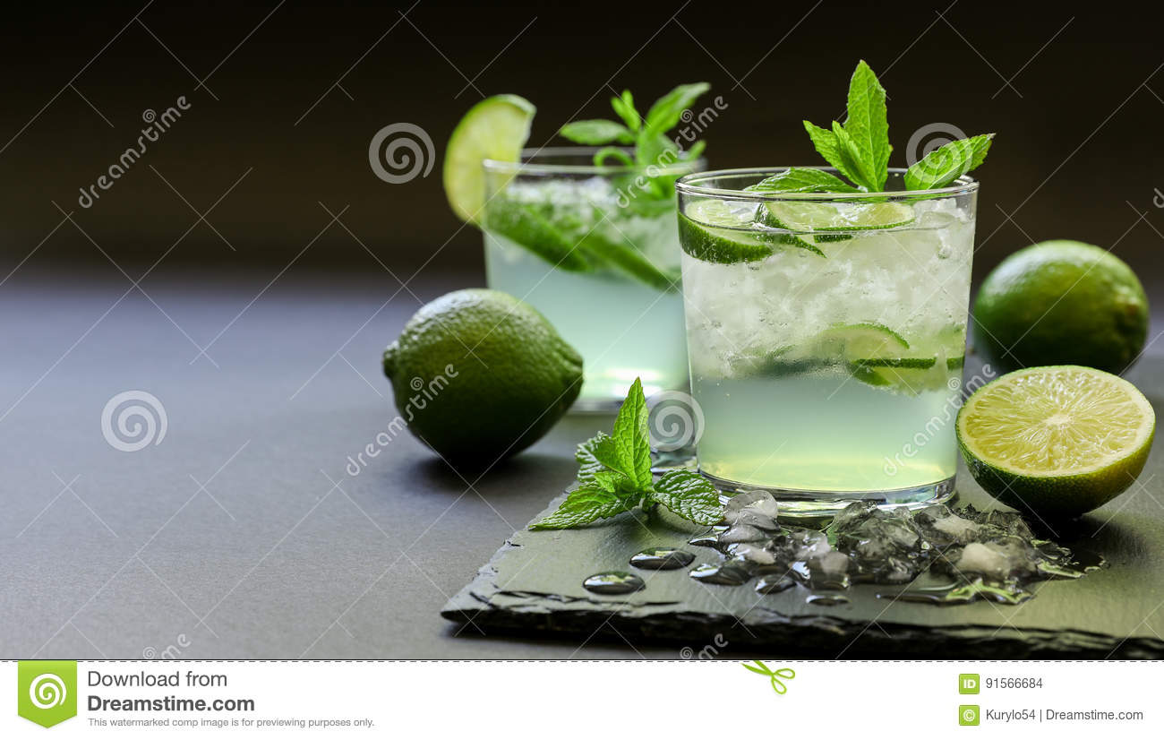 Cold cocktail with lemon liqueur, lime, tonic, ice on dark background.