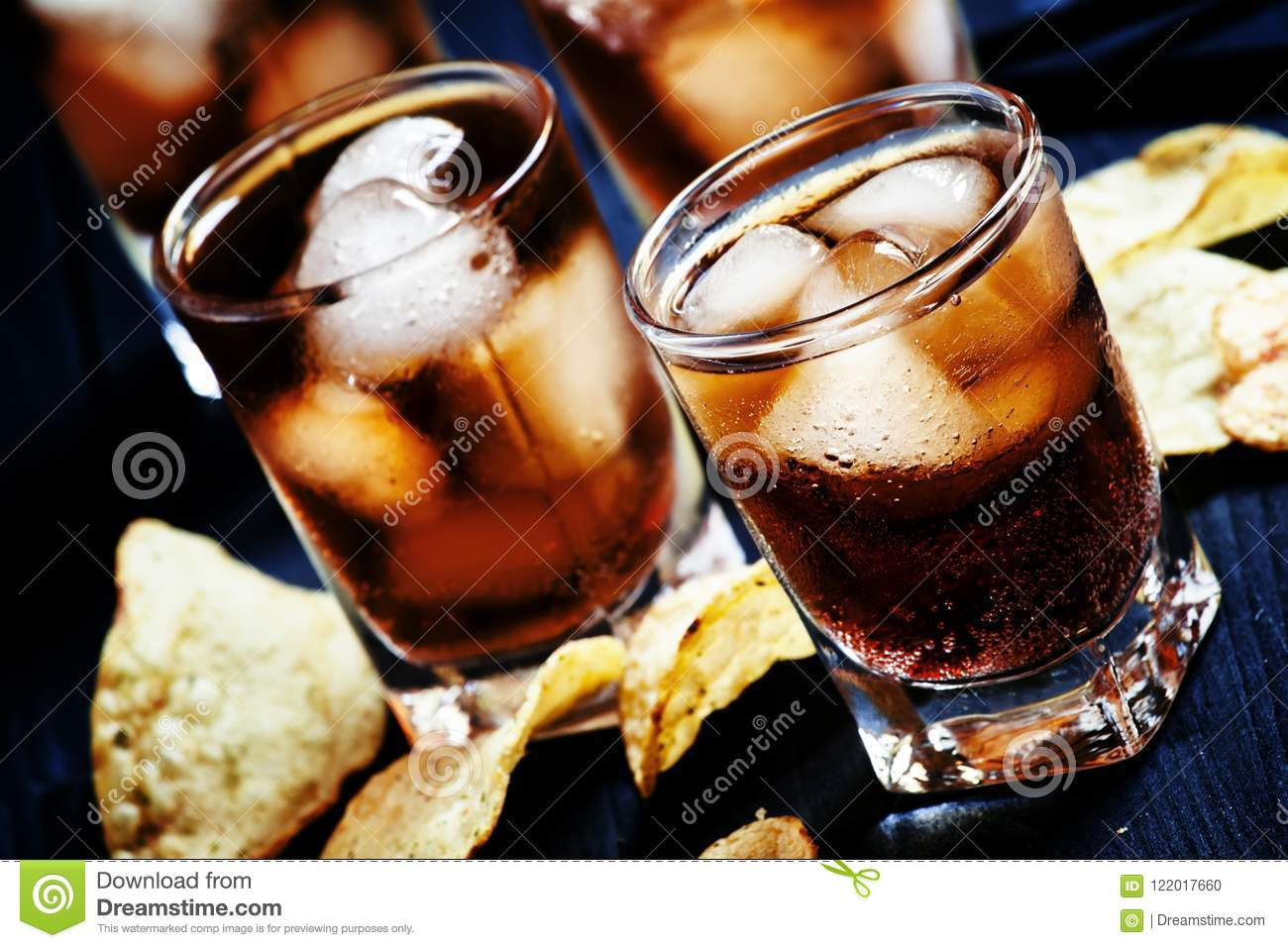 Cold Cola With Ice In Glasses And Potato Chips On A Dark