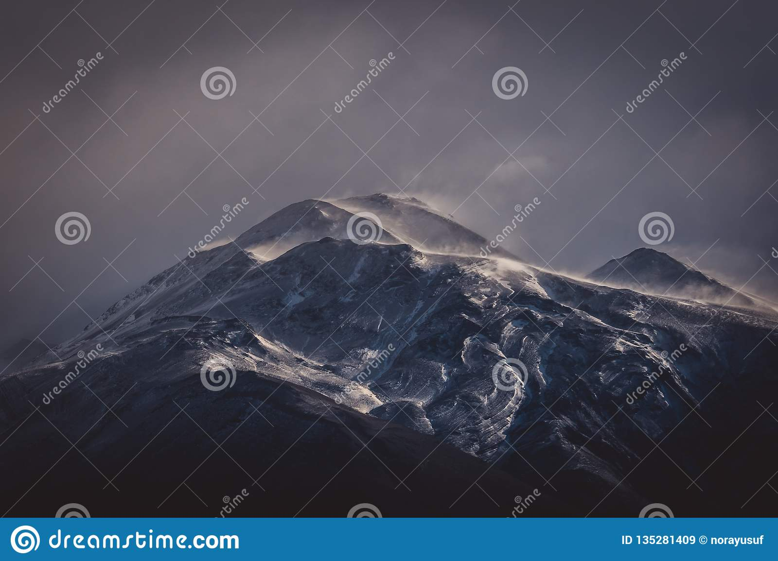 Cold grey clouds over a rugged mountain