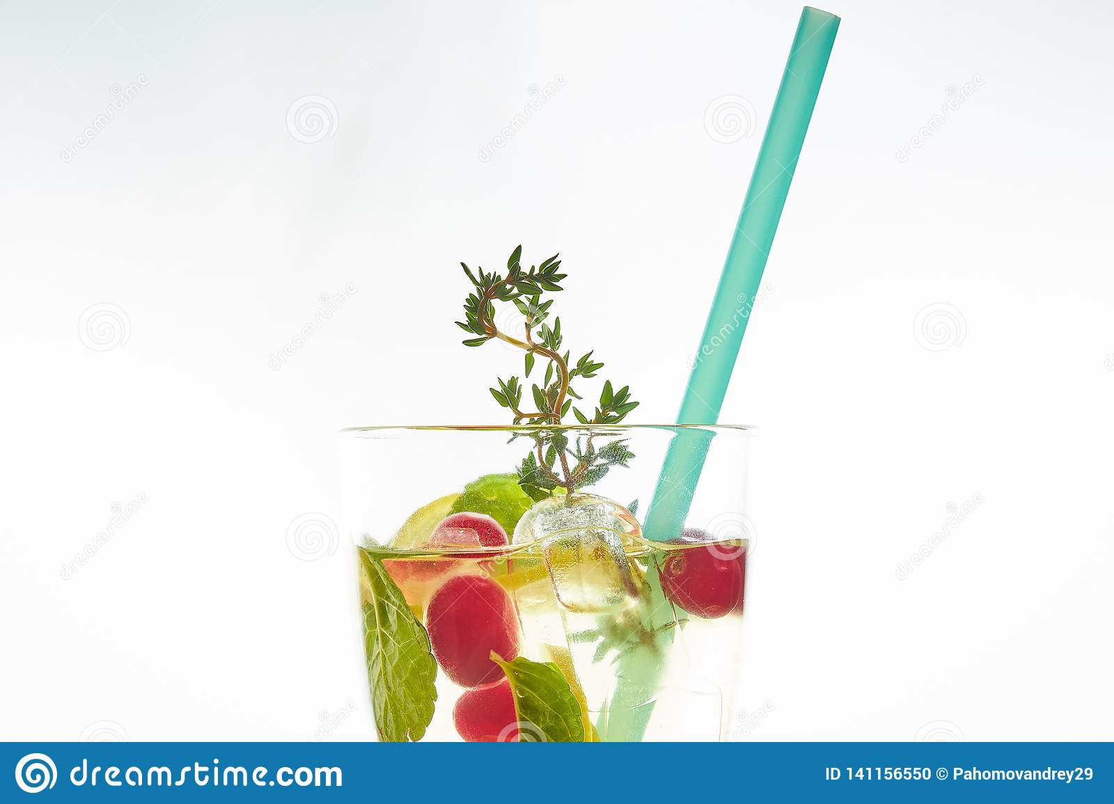 Cold mint berry cocktail in a sling isolated on white. copy space. summer refreshing drink with a straw.free space for text
