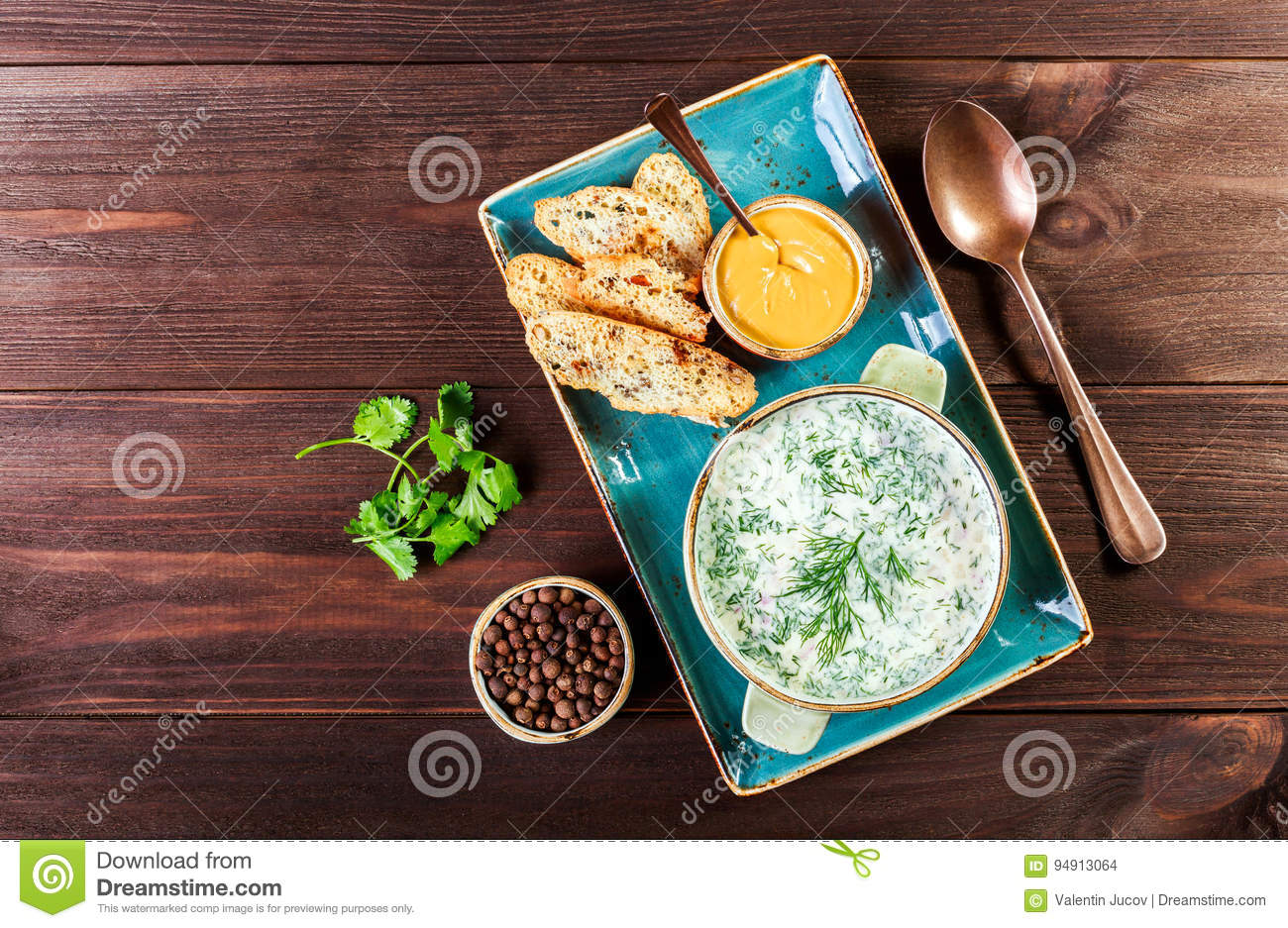 Cold soup or summer yoghurt with radish, cucumber, dill, herbs and crackers on dark wooden background. Okroshka. Homemade food.