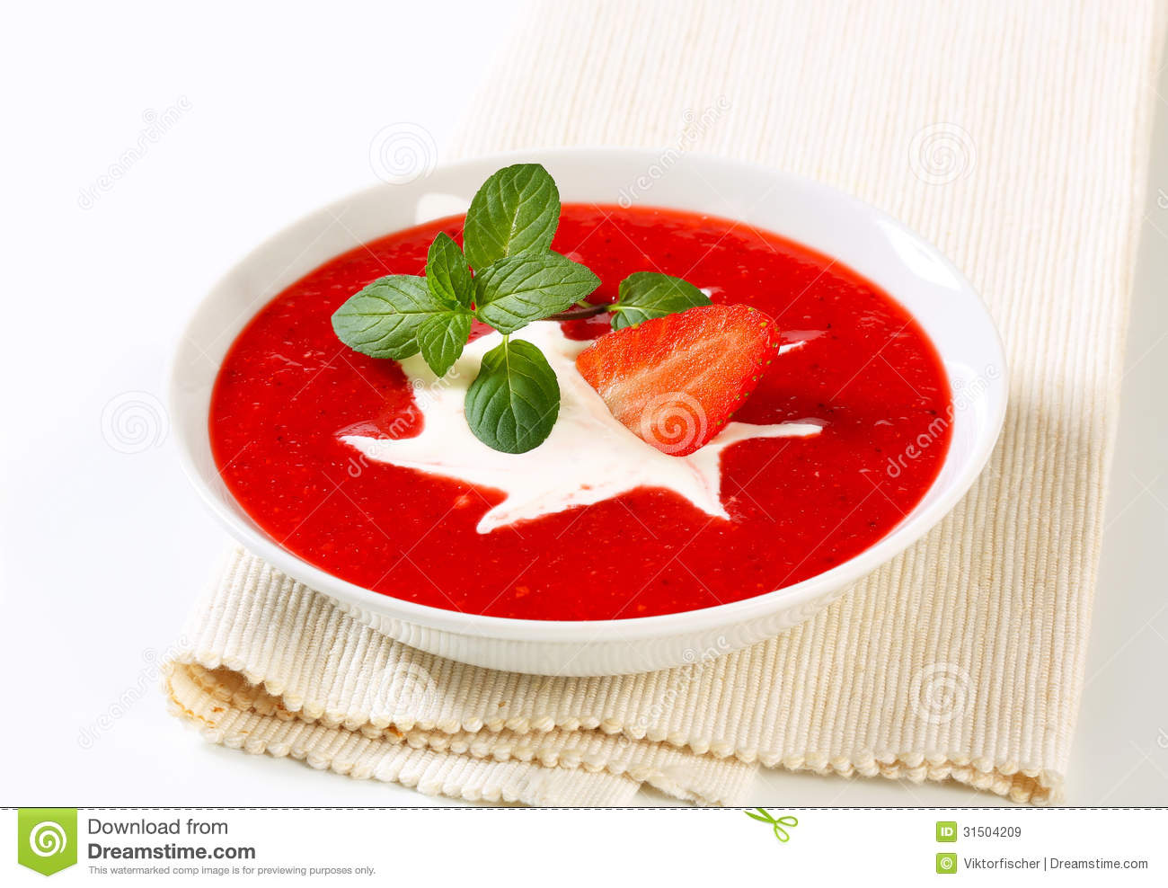 Bowl of chilled strawberry soup with cream.