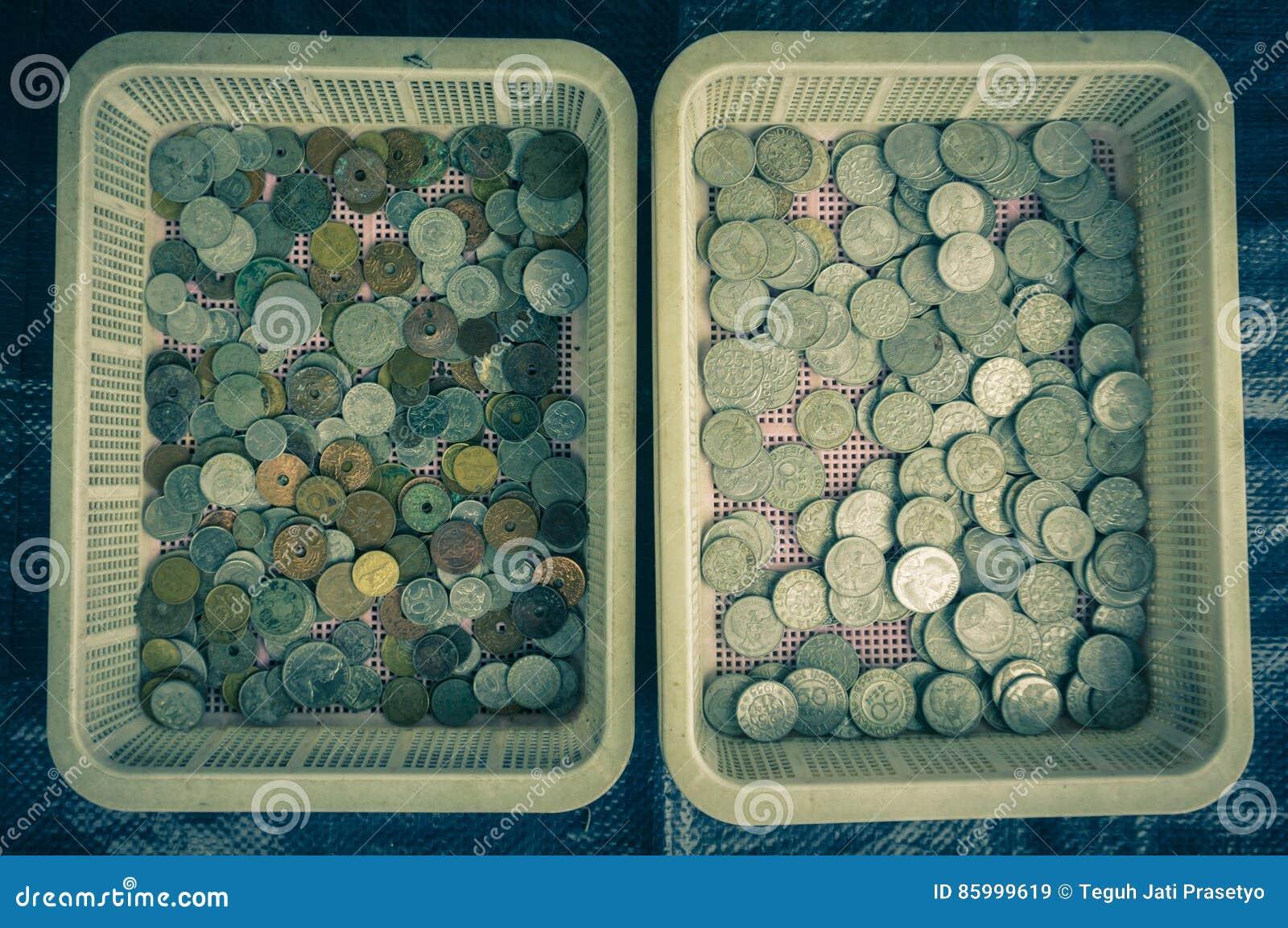 Coleção das moedas do ` s de Indonésia indicadas em uma cesta plástica Bogor recolhido foto Indonésia