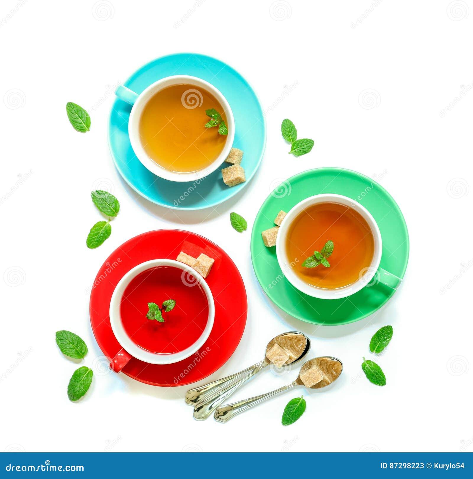 Colección del té de tres diversos tipos del té - menta, hibisco y infusión de hierbas en las tazas aisladas en blanco