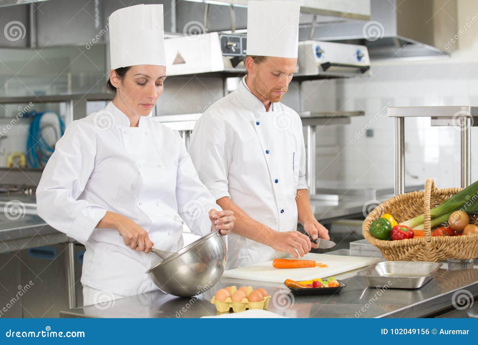 Colega de enseñanza del cocinero cómo cortar verduras en cocina