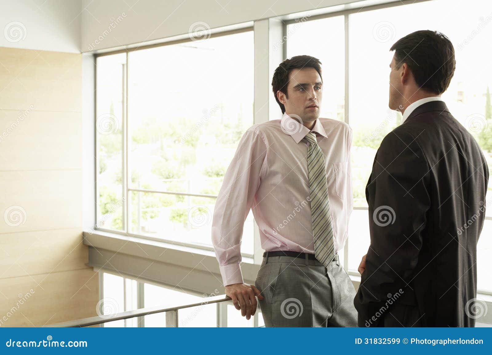 Colega de Looking At Male del hombre de negocios cercando con barandilla en oficina