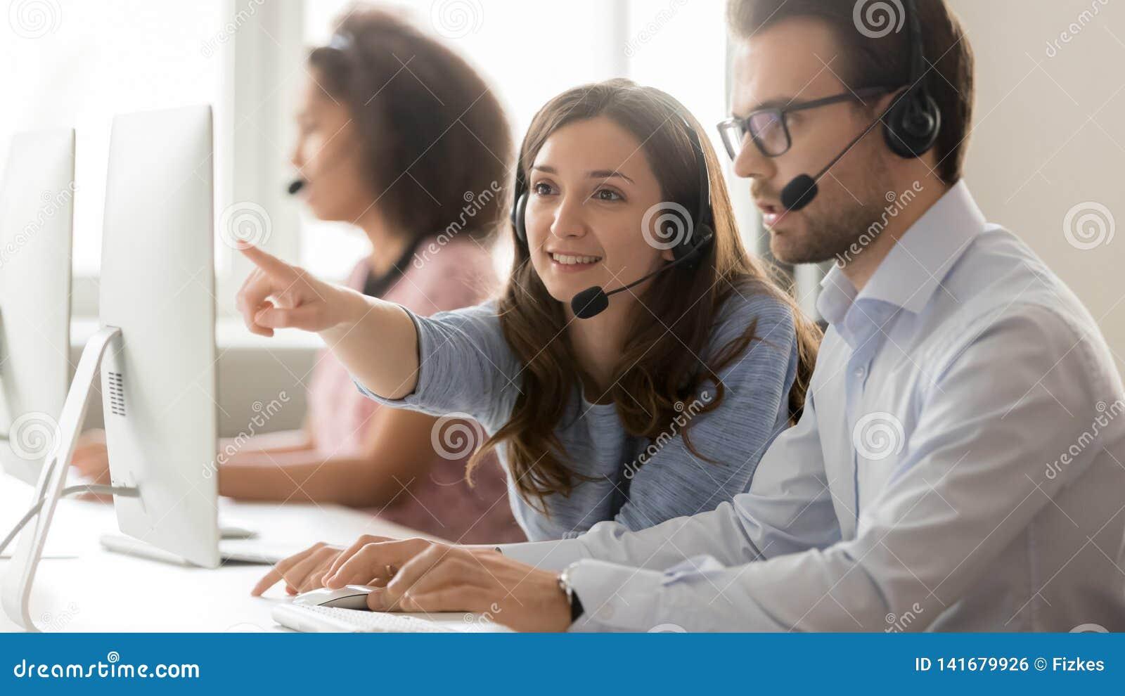 Colega masculino de ajuda do agente fêmea do centro de atendimento que aponta no computador