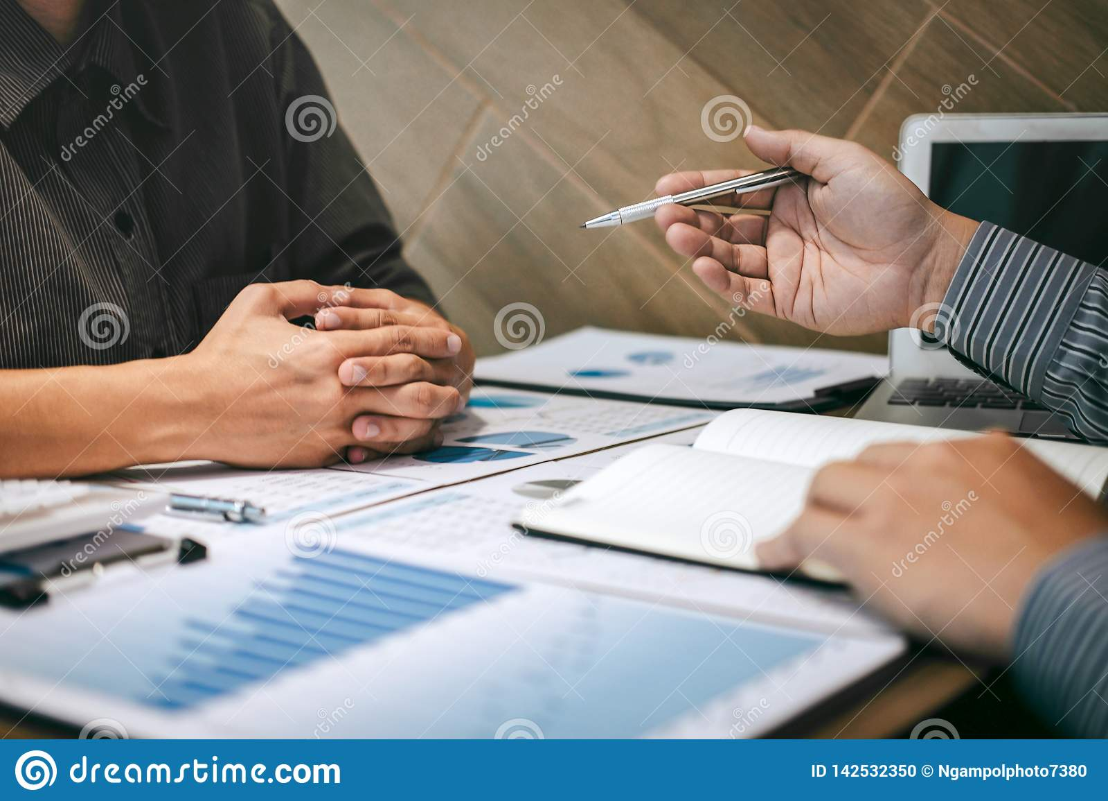 Colegas da equipe dois do negócio que fazem a conversação com projeto da apresentação do sócio em encontrar o trabalho e a anális