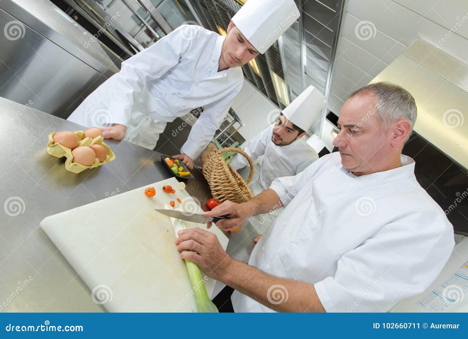 Colegas de enseñanza del chef cómo cortar verduras