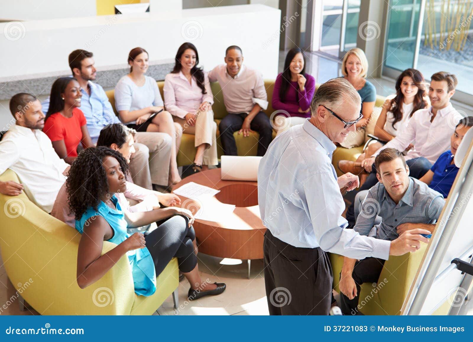 Colegas de escritório de Making Presentation To do homem de negócios