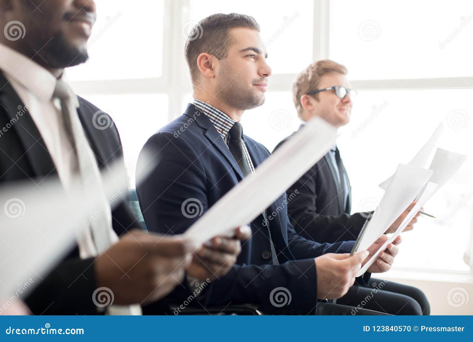 Colegas de trabalho satisfeitos que escutam a apresentação