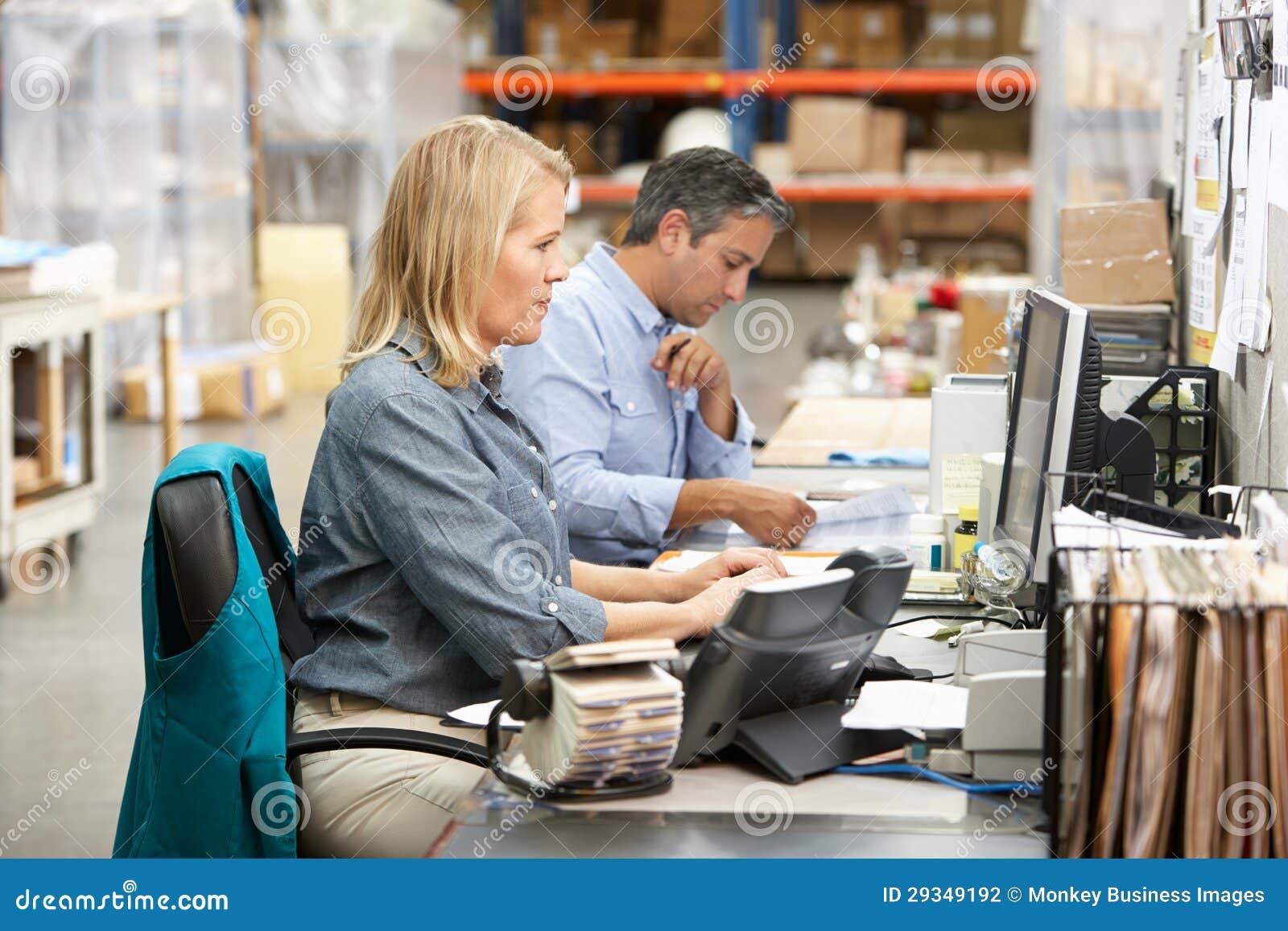 Colegas del asunto que trabajan en el escritorio en Warehouse