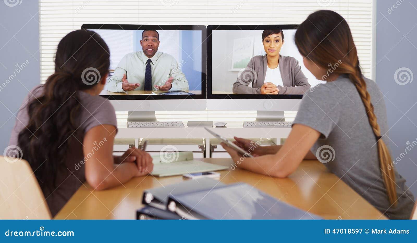 Colegas diversos do negócio que realizam uma reunião da videoconferência