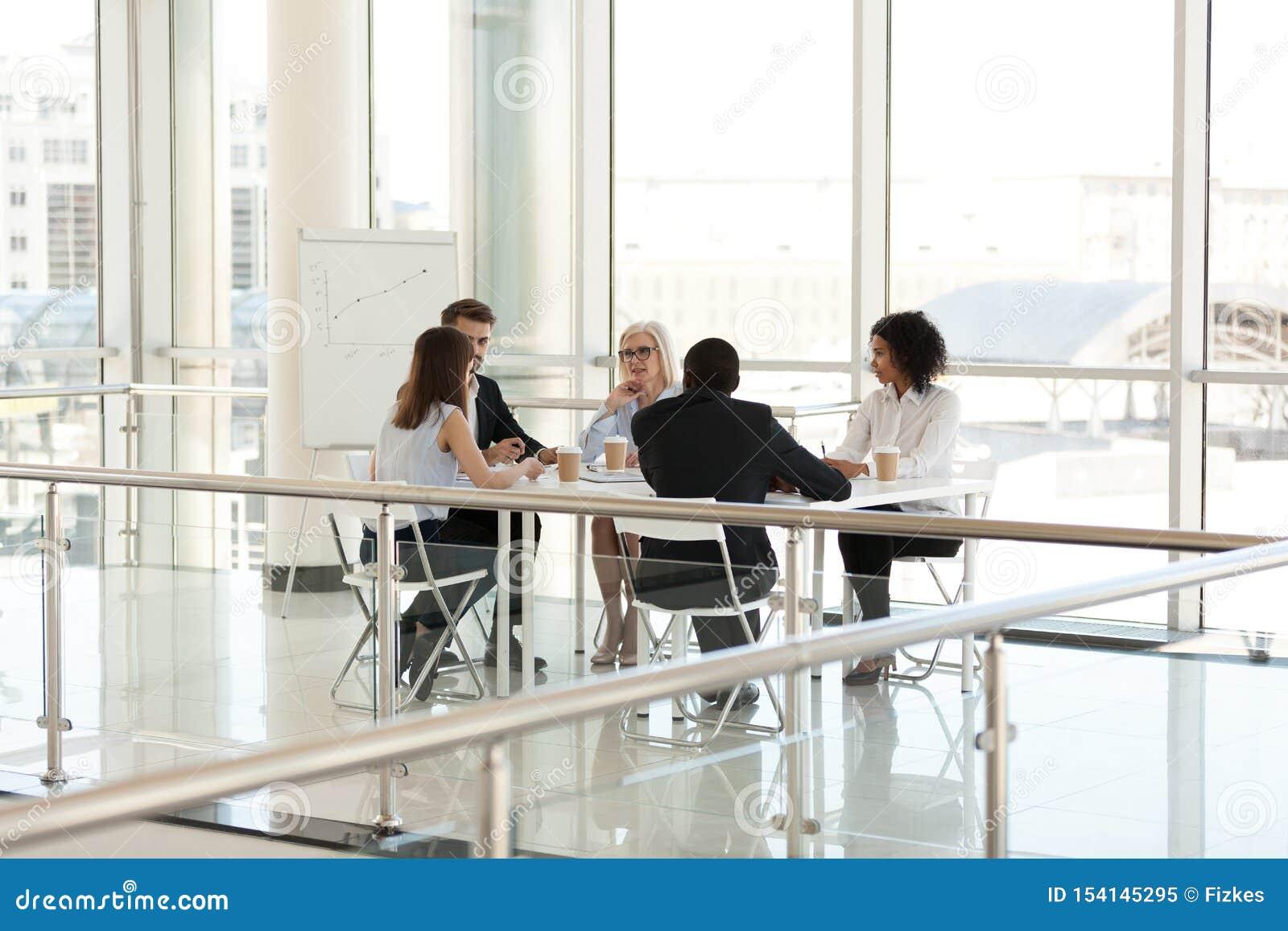 Colegas diversos que discutem o projeto na reunião de empresa na sala de direção