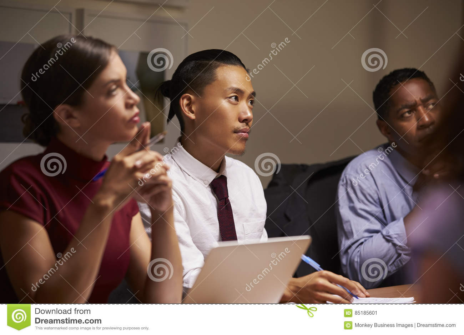 Colegas do negócio que escutam na reunião da noite, fim acima