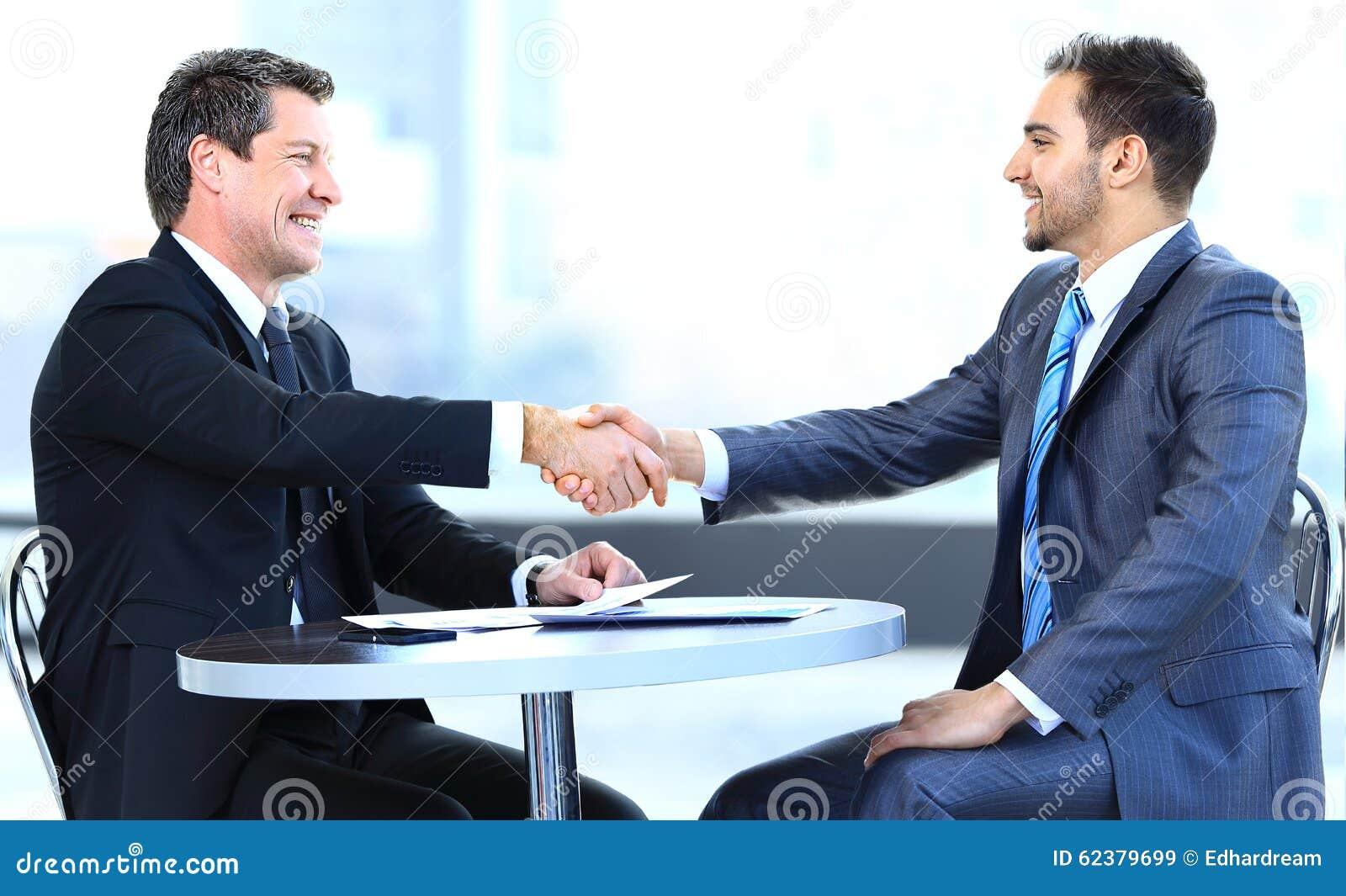 Colegas do negócio que sentam-se em uma tabela durante