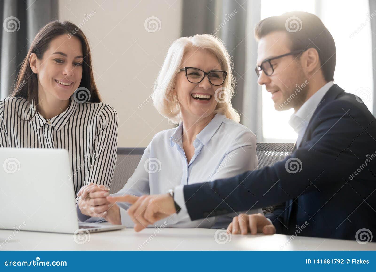 Colegas felices de la gente del equipo del negocio que hablan el trabajo de risa junto