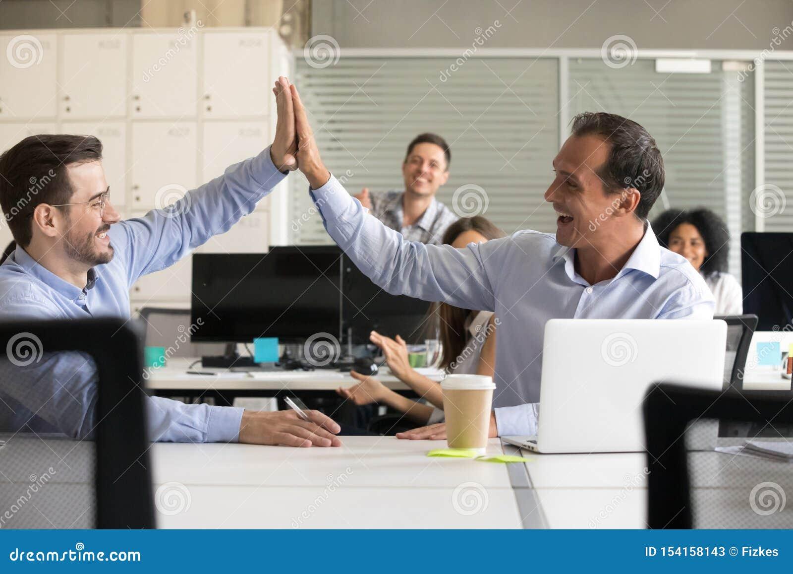 Colegas masculinos emocionados felices que dan arriba cinco en el trabajo