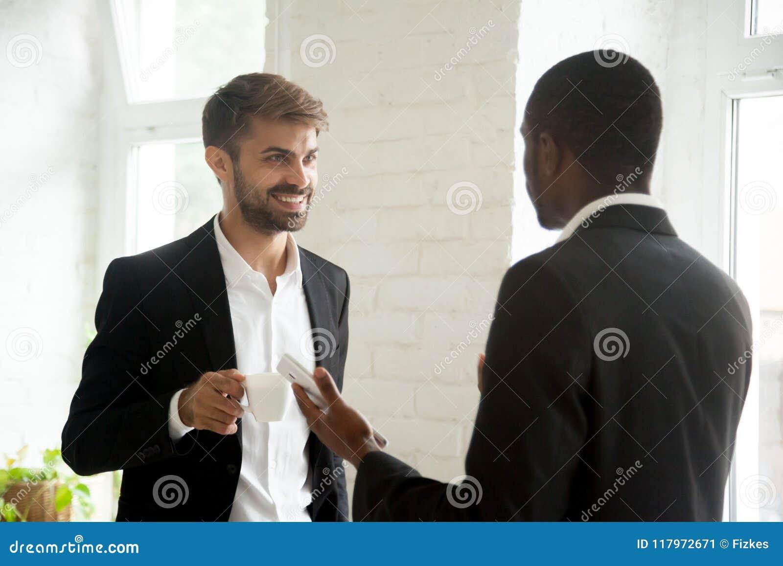 Colegas multiétnicos que tienen conversación del negocio durante coffe