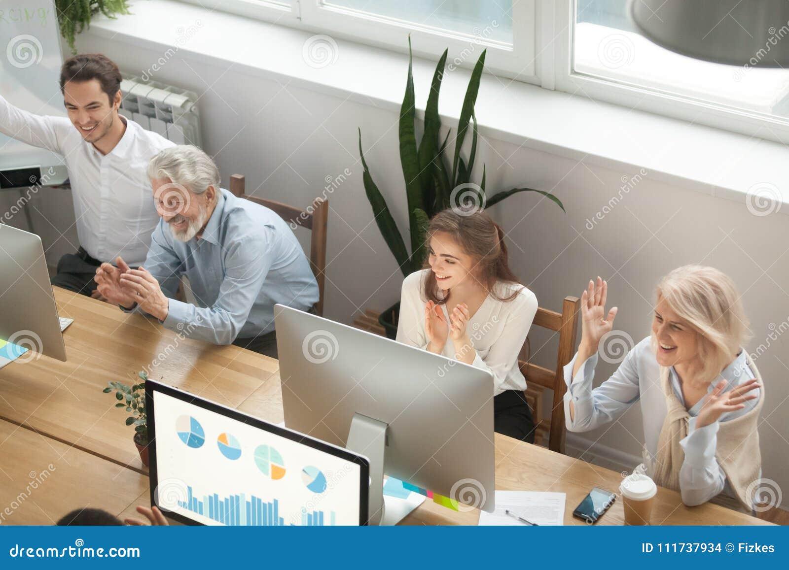 Colegas novos e idosos motivado entusiasmado que aplaudem o celebratin
