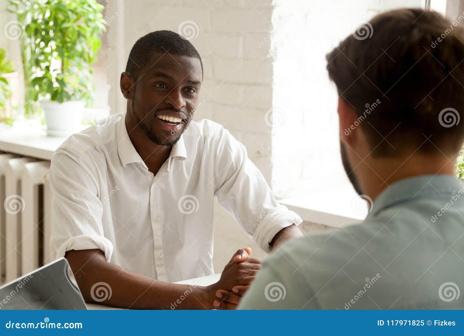 Colegas que têm a conversação que conversa no local de trabalho