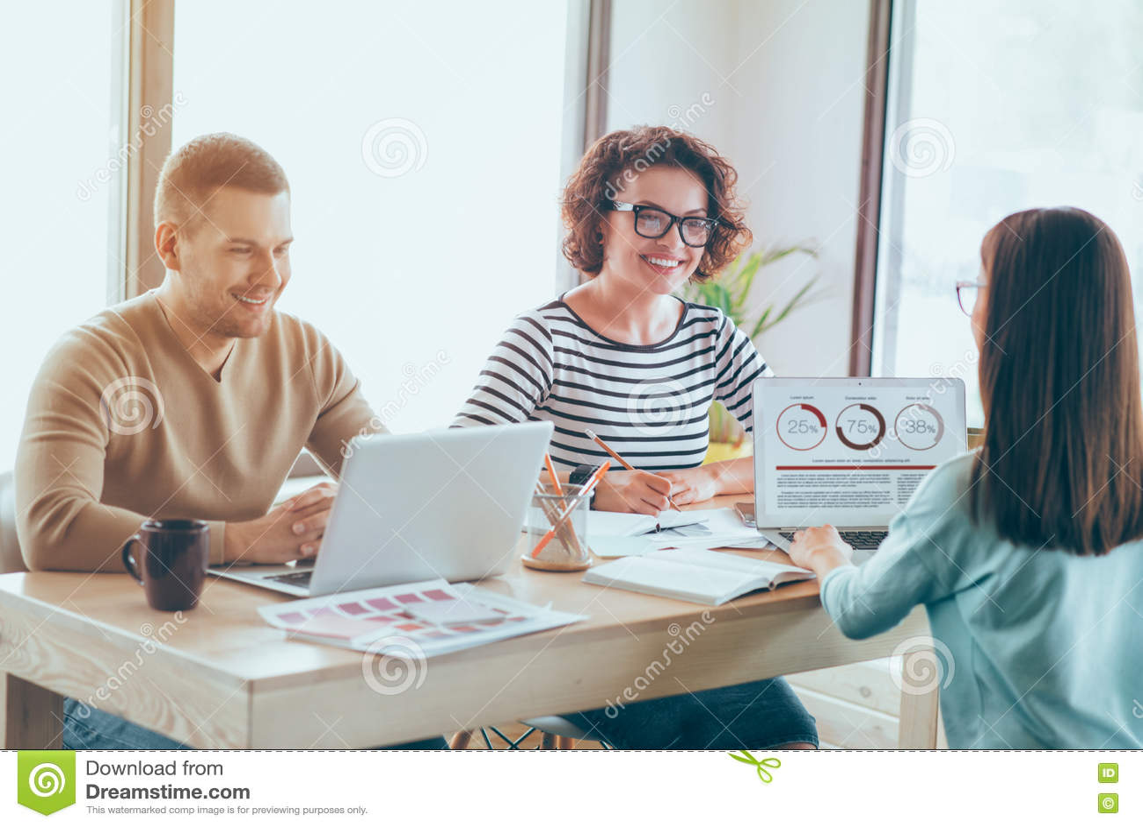 Colegas sonrientes positivos que trabajan en la tabla