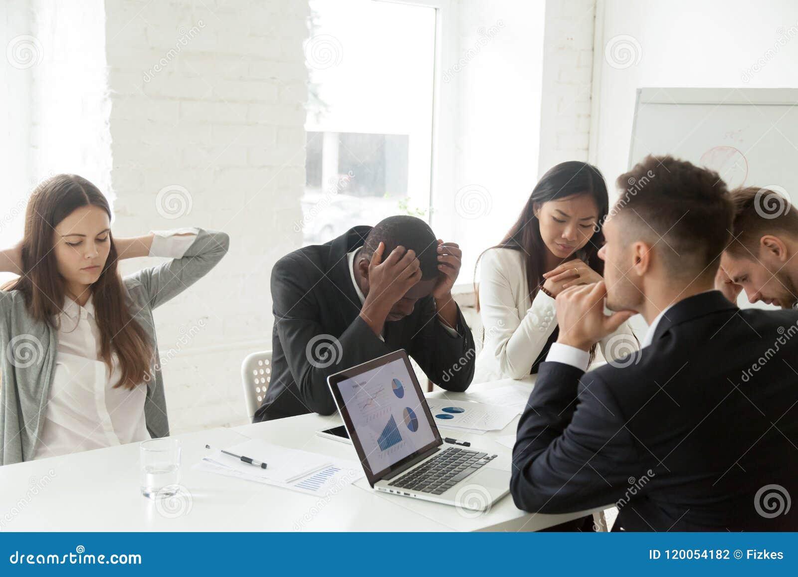 Colegas trastornados que sienten abajo debido a noticias de la quiebra de compañía
