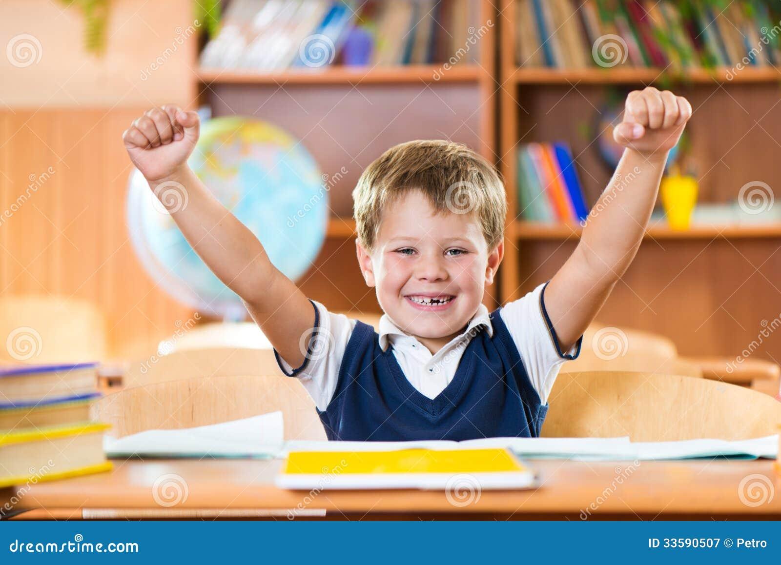 Colegial acertado con las manos que se incorporan en el escritorio