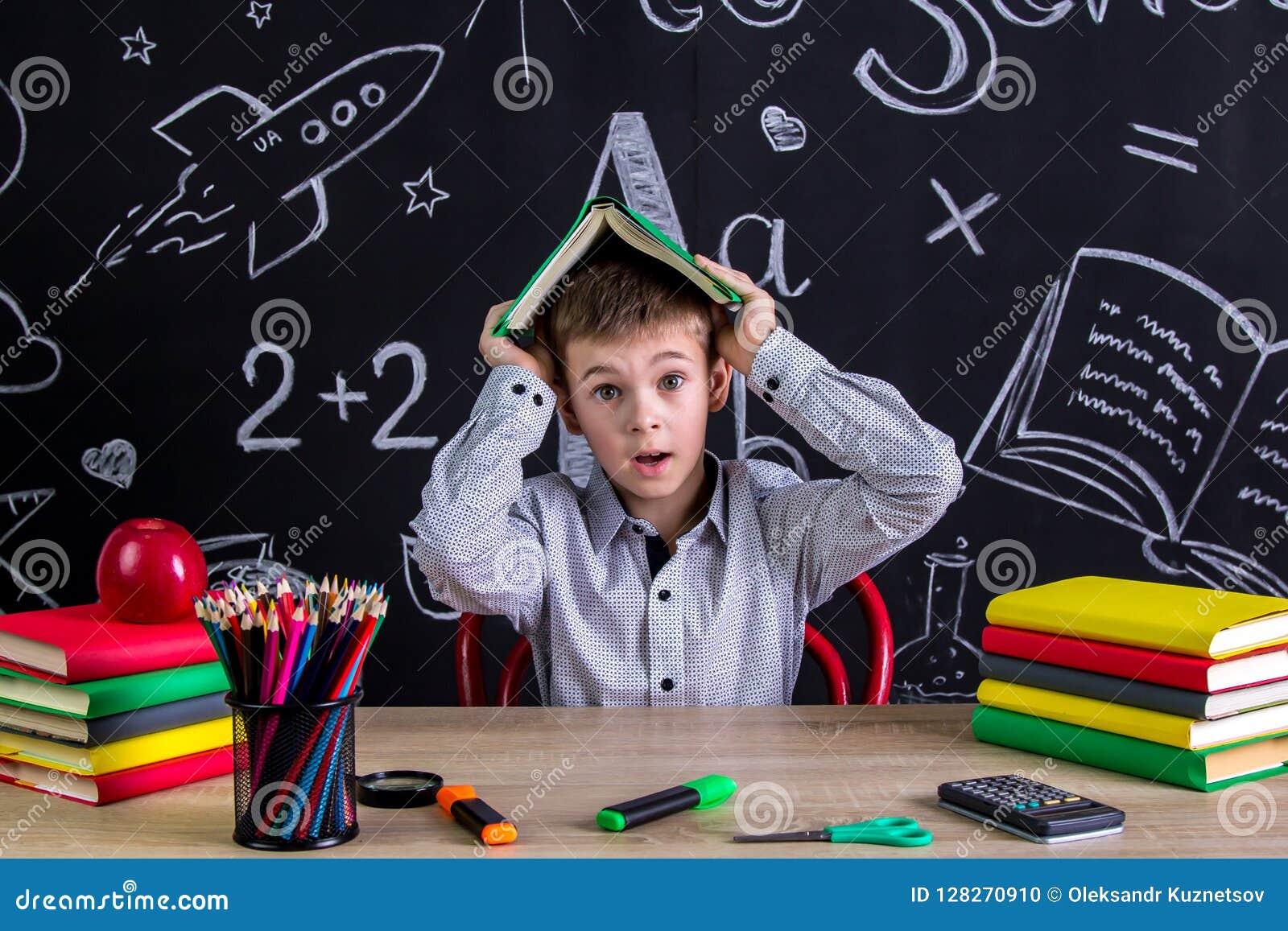 Colegial asustado y desconcertado que se sienta en el escritorio que sostiene el libro sobre la cabeza, rodeada con las fuentes d
