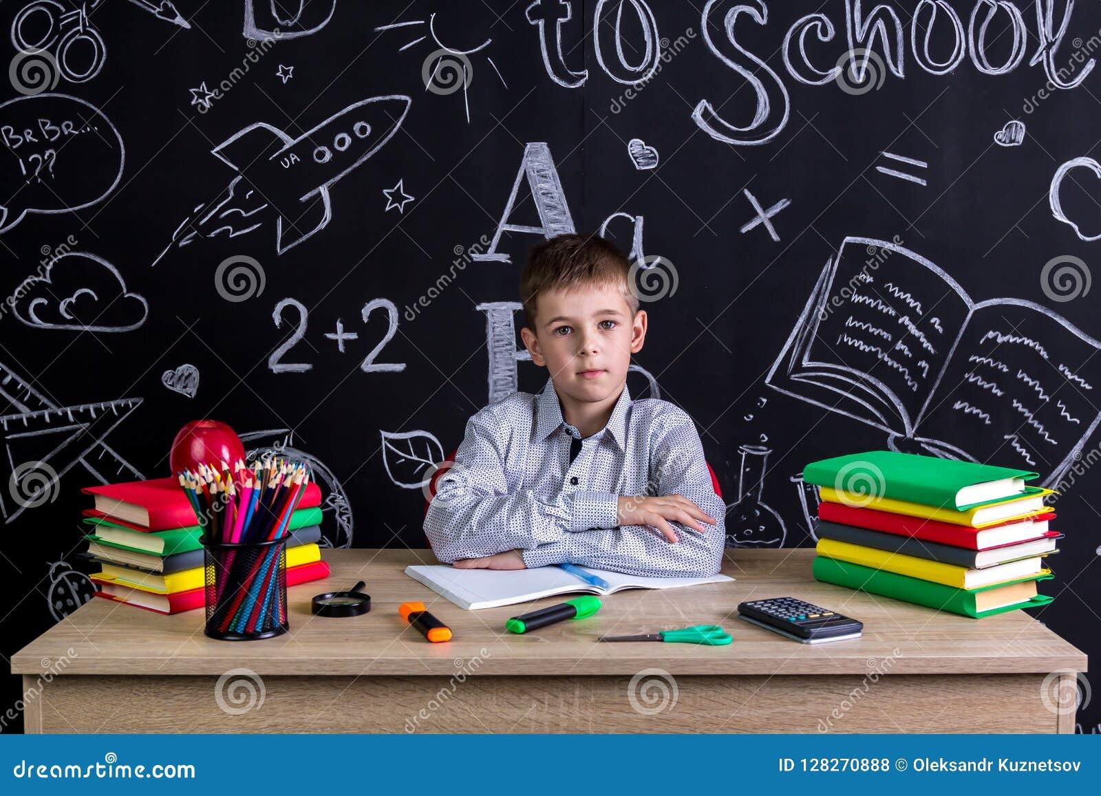 Colegial excelente serio que se sienta en el escritorio con los libros, fuentes de escuela, con ambos brazos inclinados uno a otr