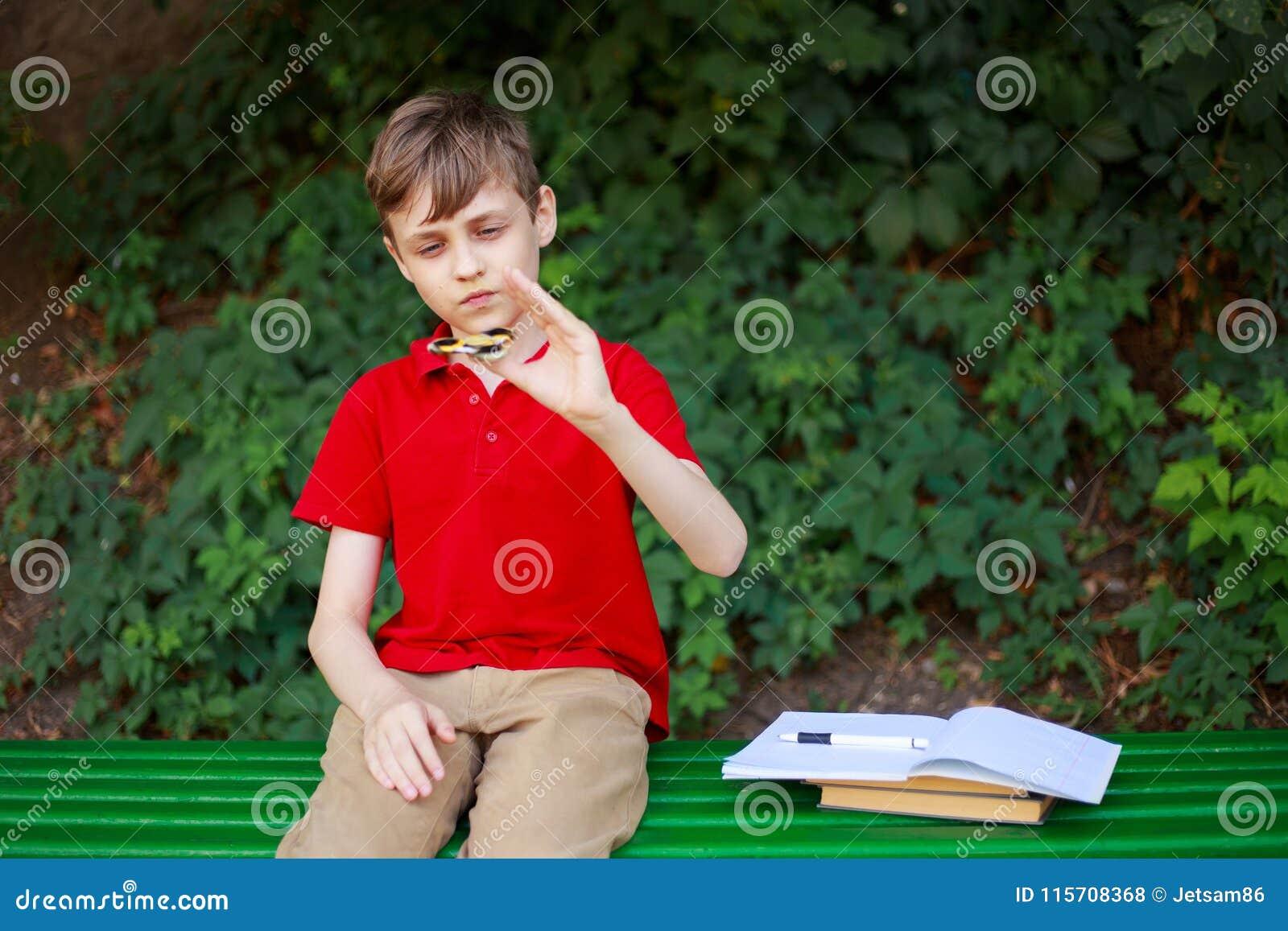 Colegial que juega con el hilandero de la persona agitada en vez de hacer la tarea casera