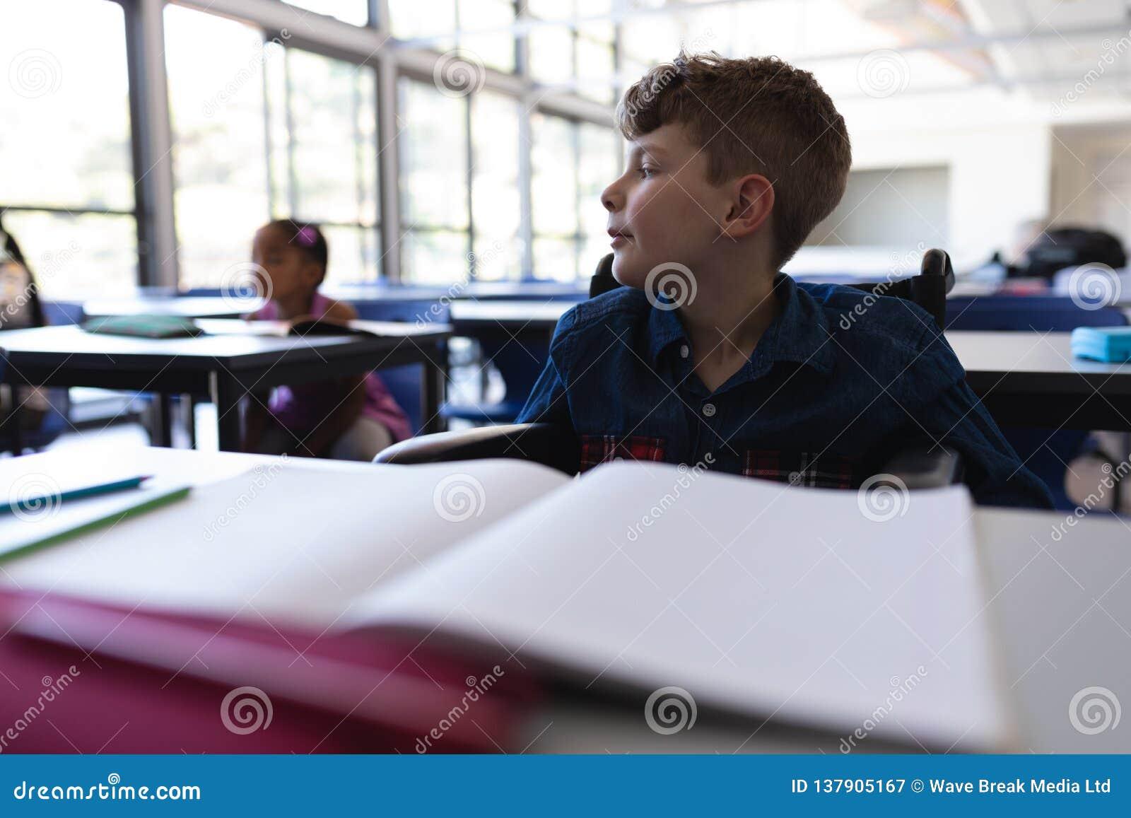 Colegial que se sienta en el escritorio y que mira lejos en sala de clase