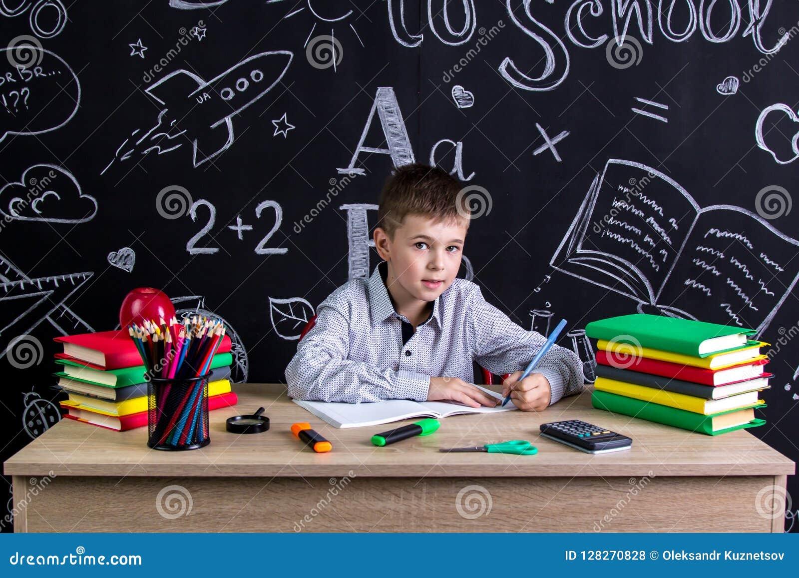 Colegial zurdo que se sienta en el escritorio con los libros, fuentes de escuela, escribiendo en el libro de ejercicio, mirando d
