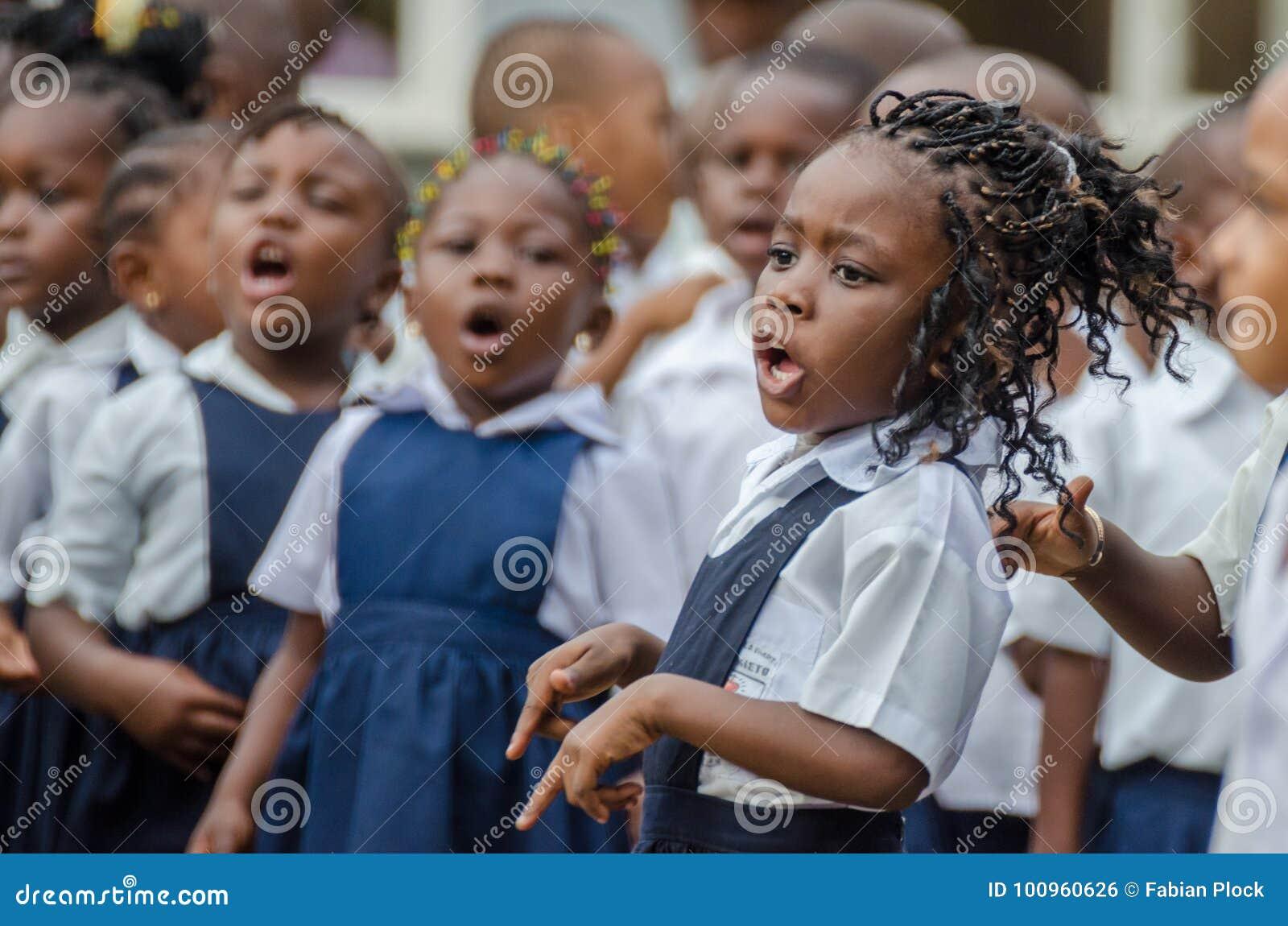 Colegiala africana joven con el pelo maravillosamente adornado que canta y que baila en el preescolar en Matadi, Congo, África