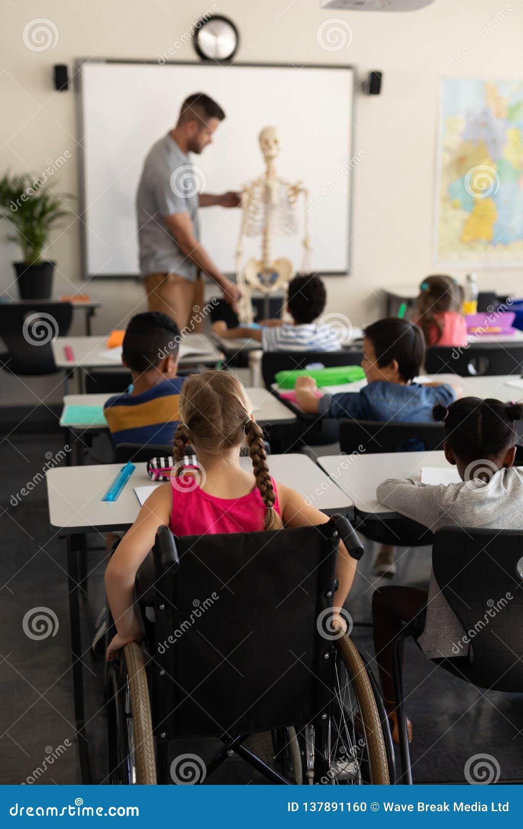 Colegiala de la neutralización con el compañero de clase que estudia en la sala de clase que se sienta en el escritorio de la esc