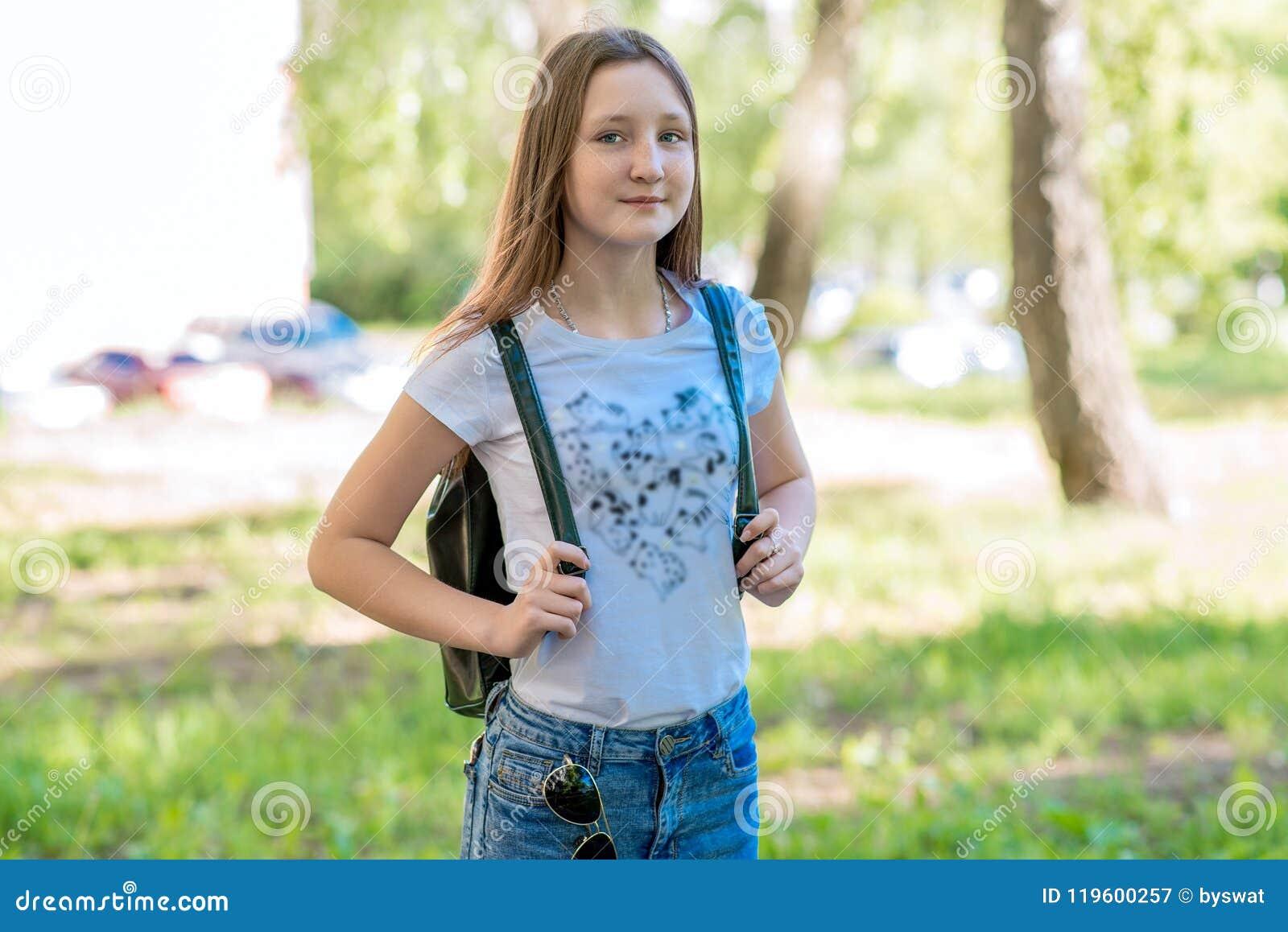 Colegiala de la niña En el verano en el parque Actitudes en la cámara  detrás de la mochila Sonrisa feliz después de escuela camping