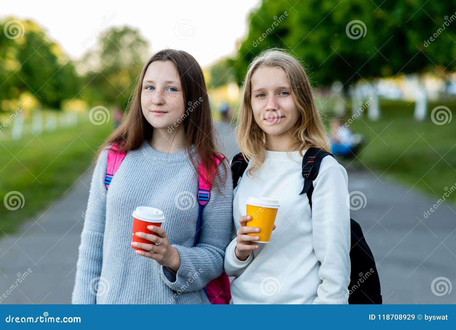 Colegiala hermosa de dos chicas jóvenes En verano fuera de la ciudad en aire fresco Él sostiene té y el café calientes en sus man