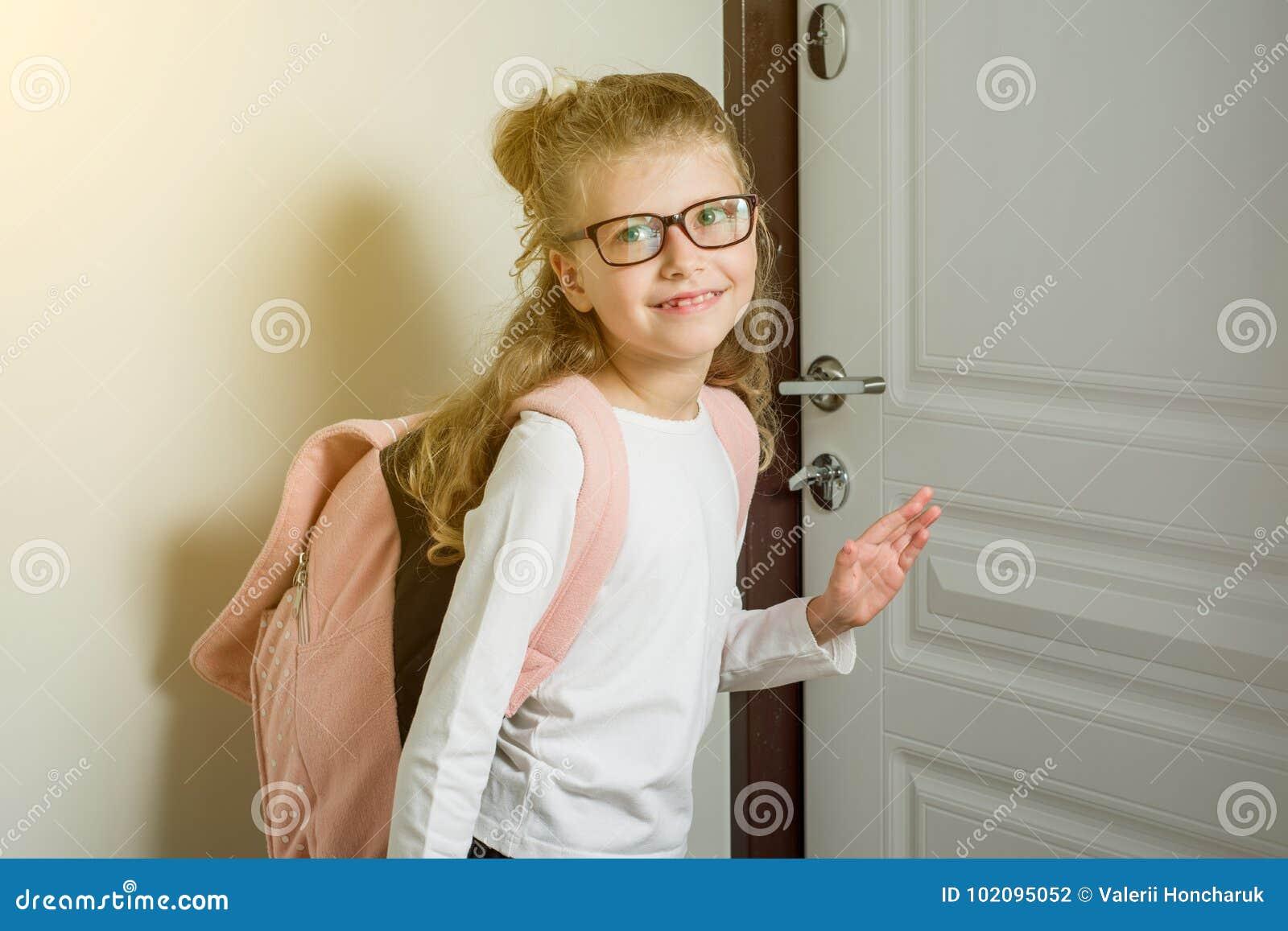 Colegiala menor linda con el pelo rubio que va a la escuela, colocándose