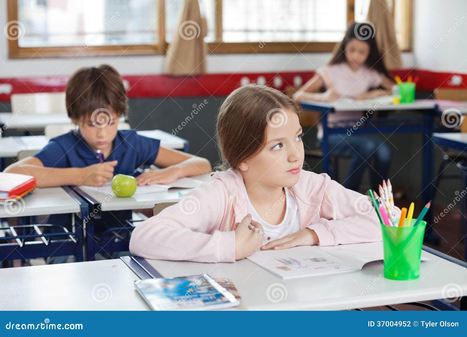Colegiala que parece ausente mientras que dibuja en sala de clase