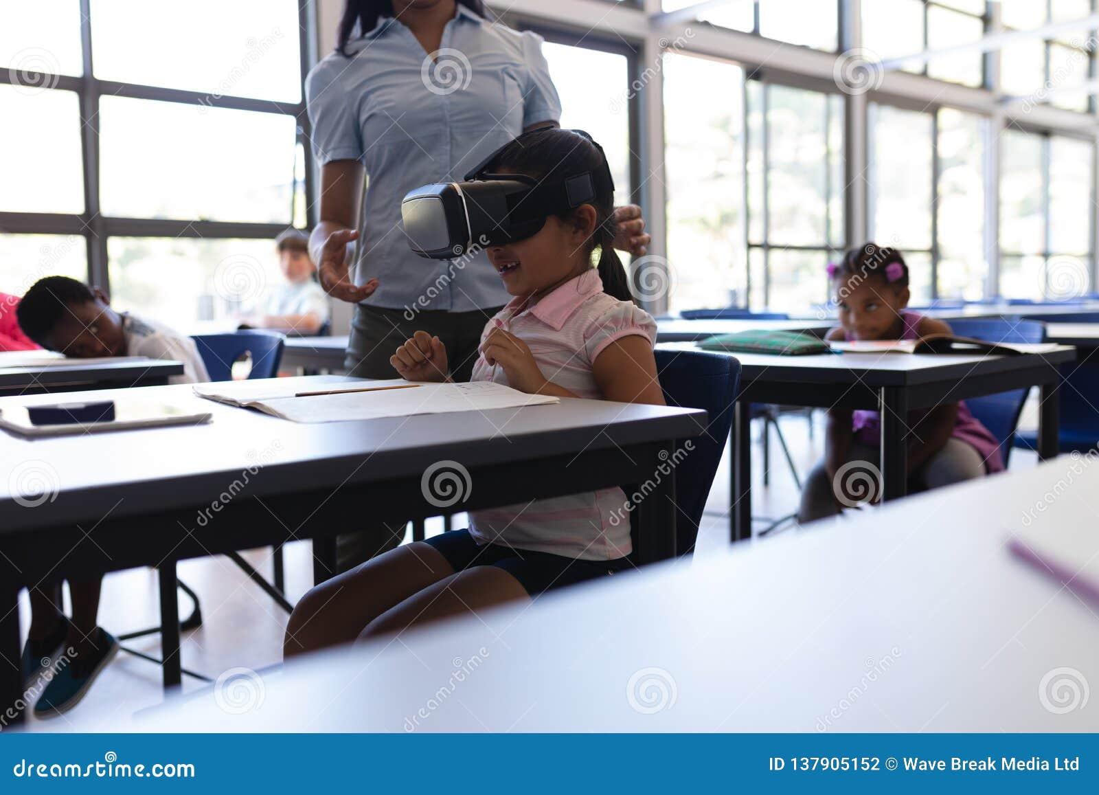 Colegiala que usa las auriculares de la realidad virtual en el escritorio en sala de clase