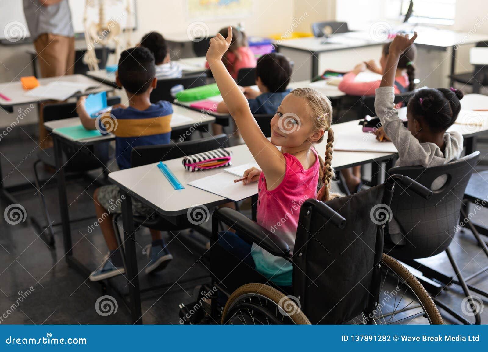 Colegiala sonriente de la neutralización que mira la cámara y el aumento de la mano en sala de clase