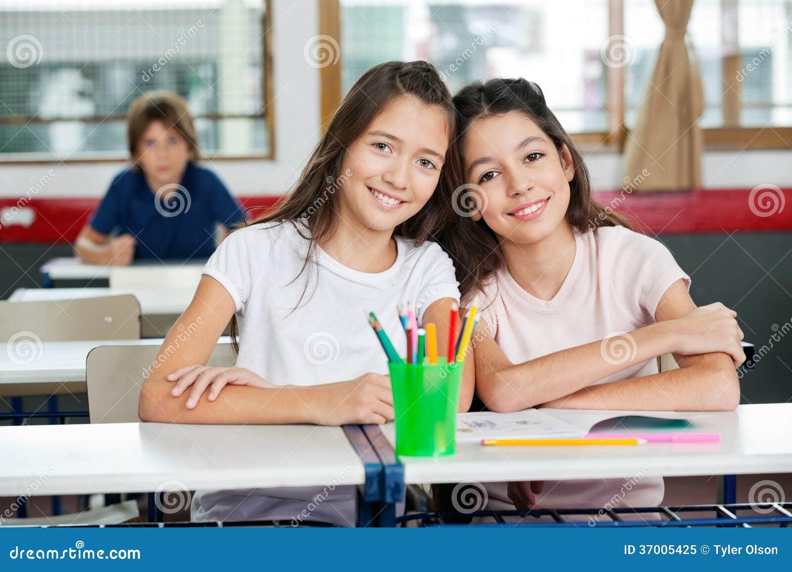 Colegialas lindas que se sientan junto en el escritorio