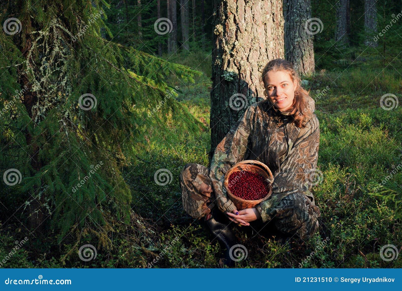 Colheita Cowberrys da mulher nova.