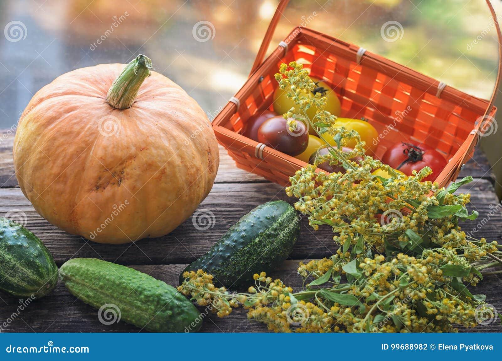 Colheita fresca de tomates vermelhos e amarelos em uma cesta de vime em uma tabela de madeira velha