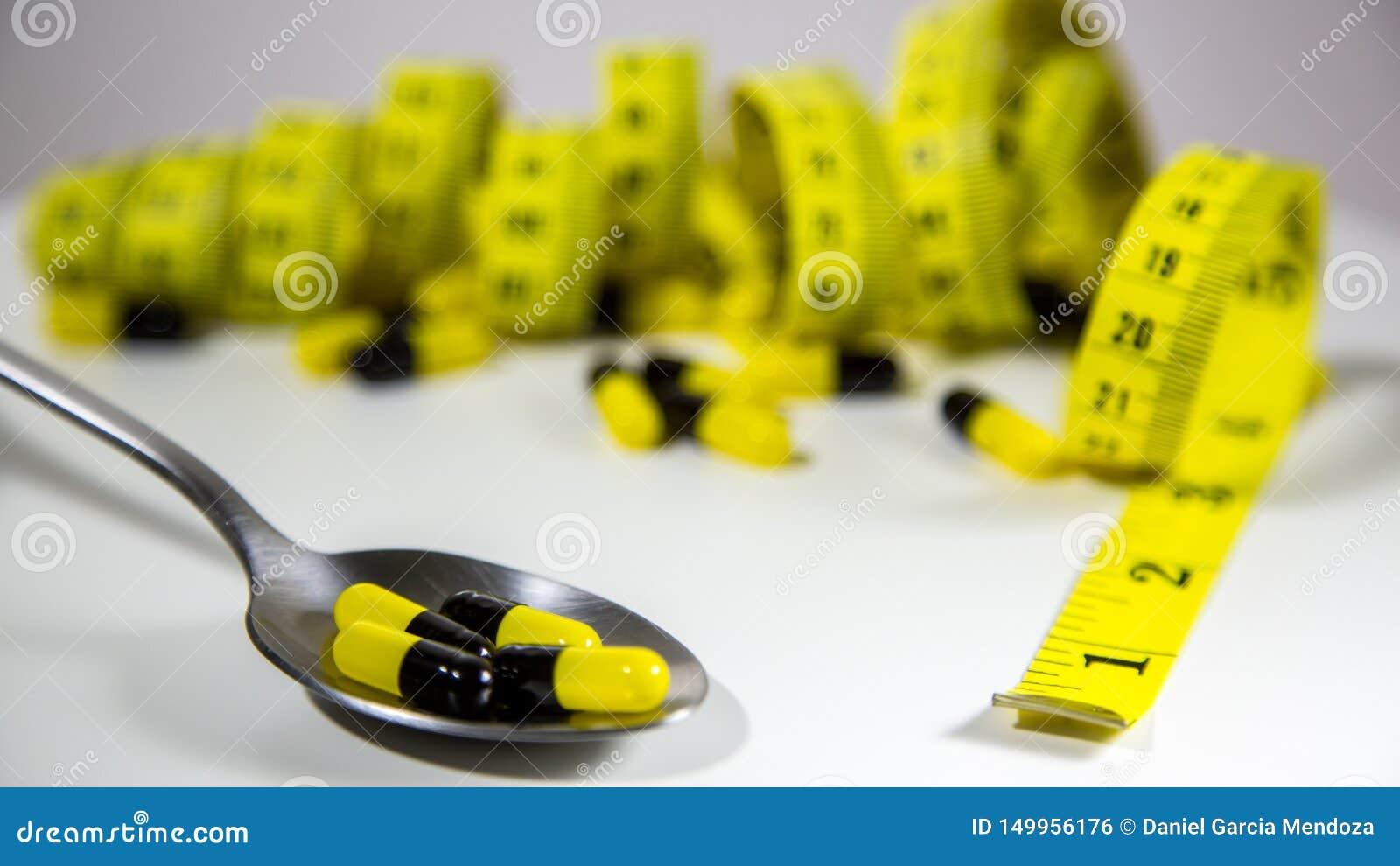 Colher com os comprimidos e a fita de medição para representar a indústria do comprimido da dieta