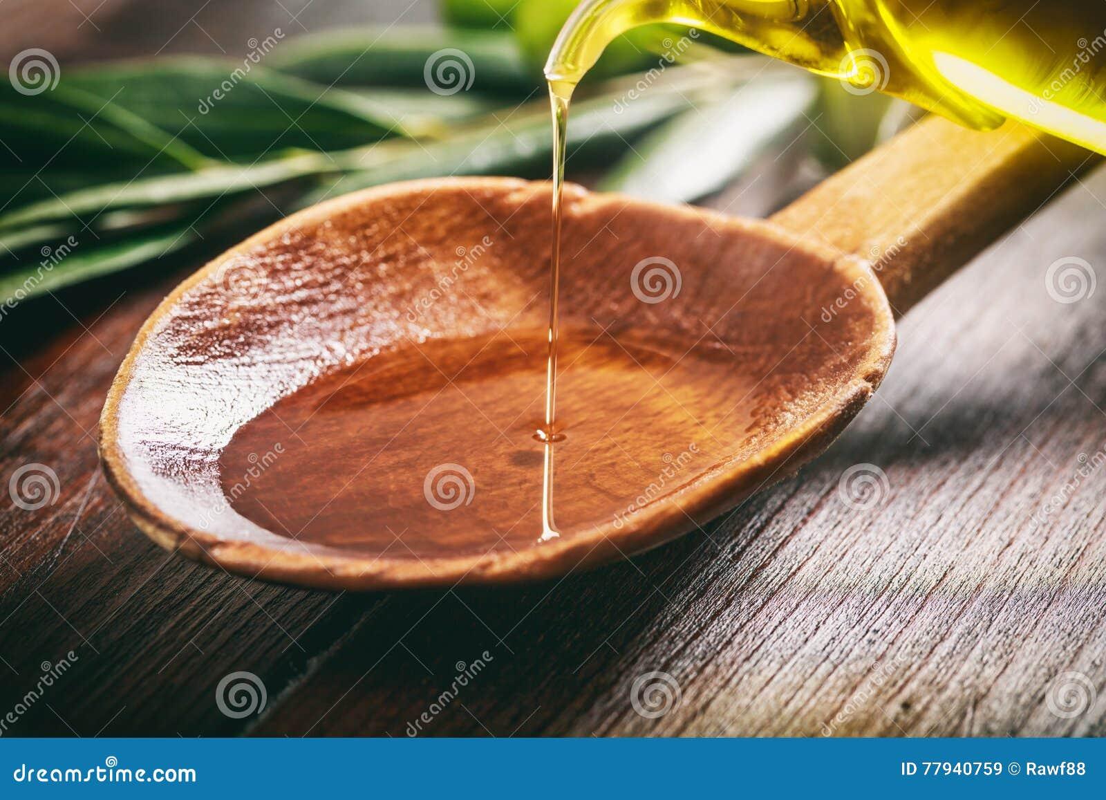 Colher de madeira com azeitonas e azeite