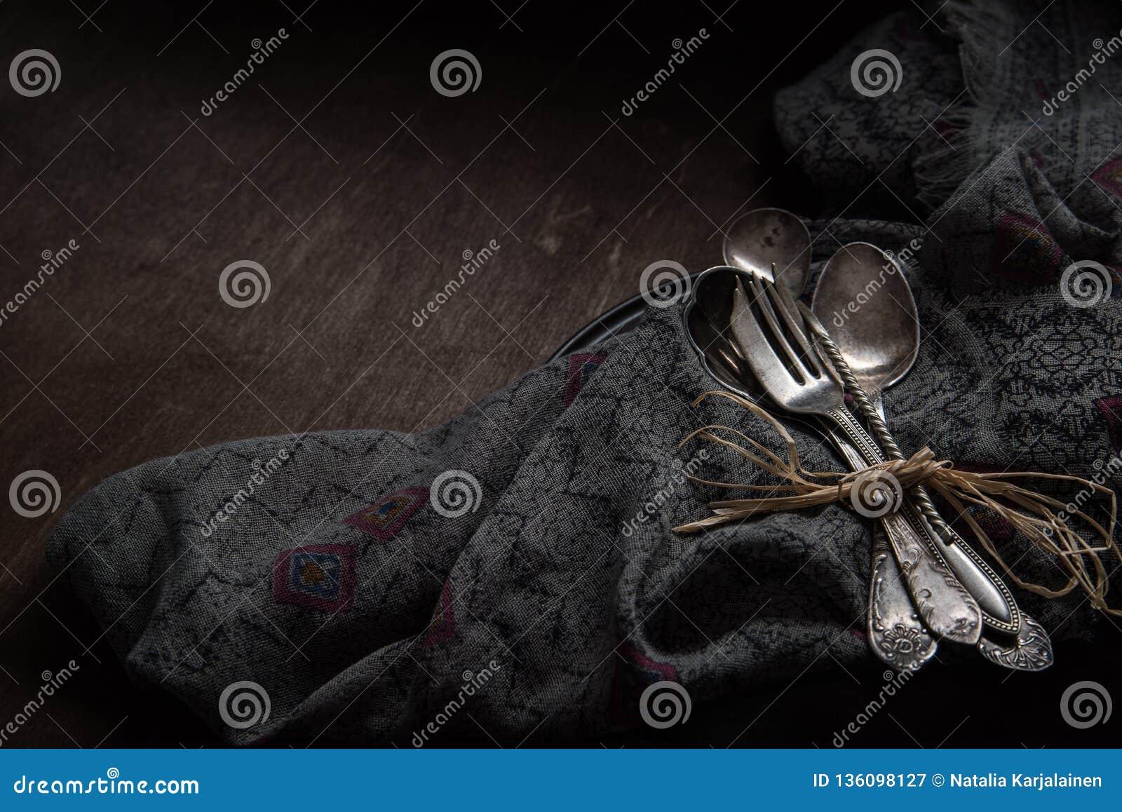Colheres, forquilhas e faca de prata do vintage no fundo preto do vintage Discreto